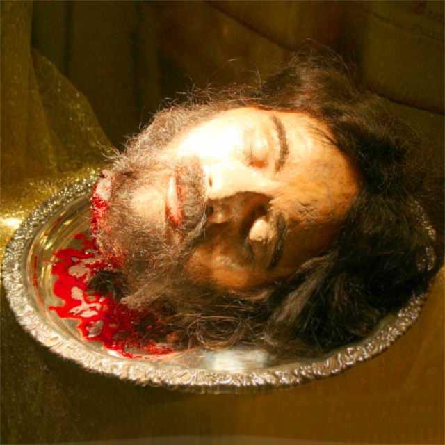 L'immagine raffigura una testa mozzata disposta su un vassoio d'argento