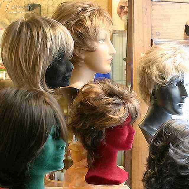 parrucche sintetiche esposte nella vetrina della bottega