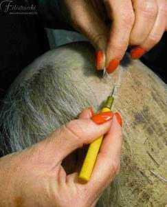 Realizzazione a mano presso la nostra bottega di Toupet da uomo in capelli naturali su silicone per riprodurre l'effetto naturale del cuoio capelluto.